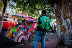 An app-based motorcycle taxi driver observes the parked Becak Pustaka. JP/Anggertimur Lanang Tinarbuko