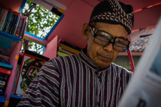 Sutopo wears two layers of glasses to help him read small fonts in books or newspapers. JP/Anggertimur Lanang Tinarbuko