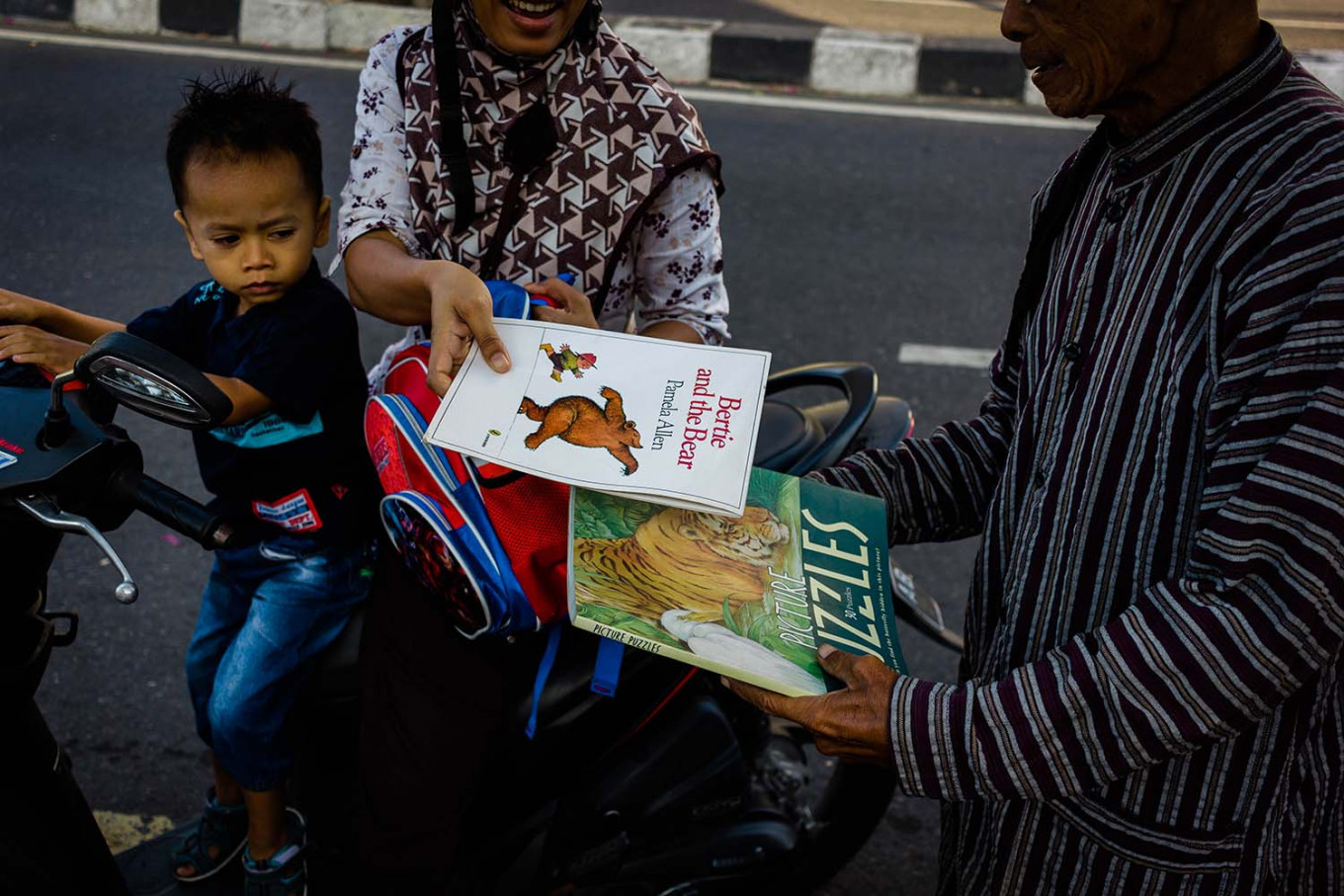 Rini and her son, Devan, return a picture book they borrowed from Sutopo's Becak Pustaka. JP/Anggertimur Lanang Tinarbuko