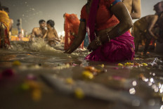 Petals float in the Ganges as men and women gather to bathe. JP/Tyler Blodgett