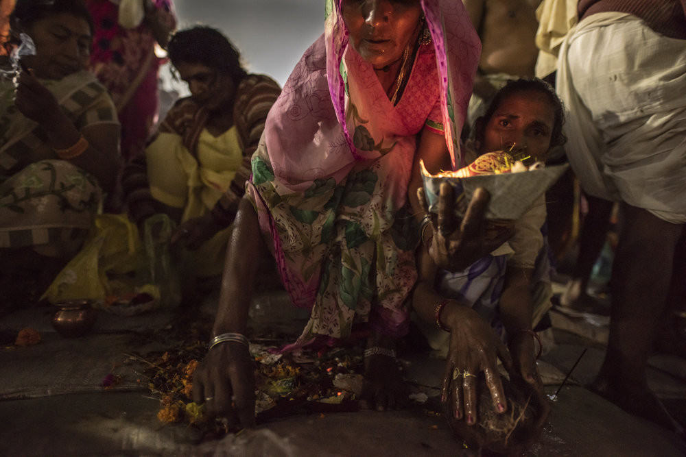 Women push through the throng to pray and offer fruit and flowers as pooja. JP/Tyler Blodgett