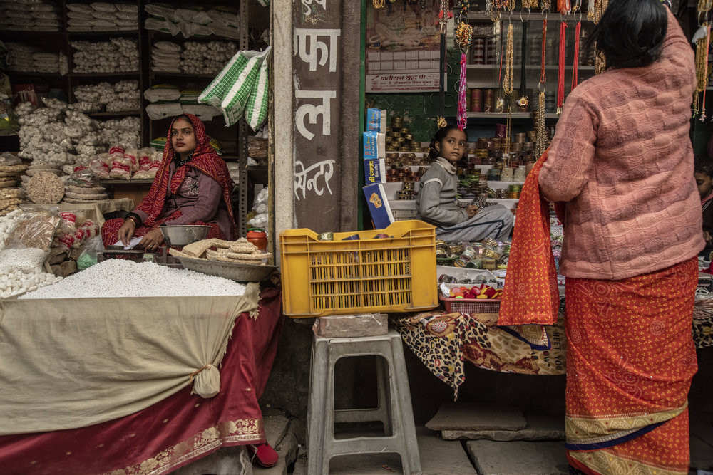 A woman and a young girl in a market in Allahabad, though divided, share the same expression. JP/Tyler Blodgett