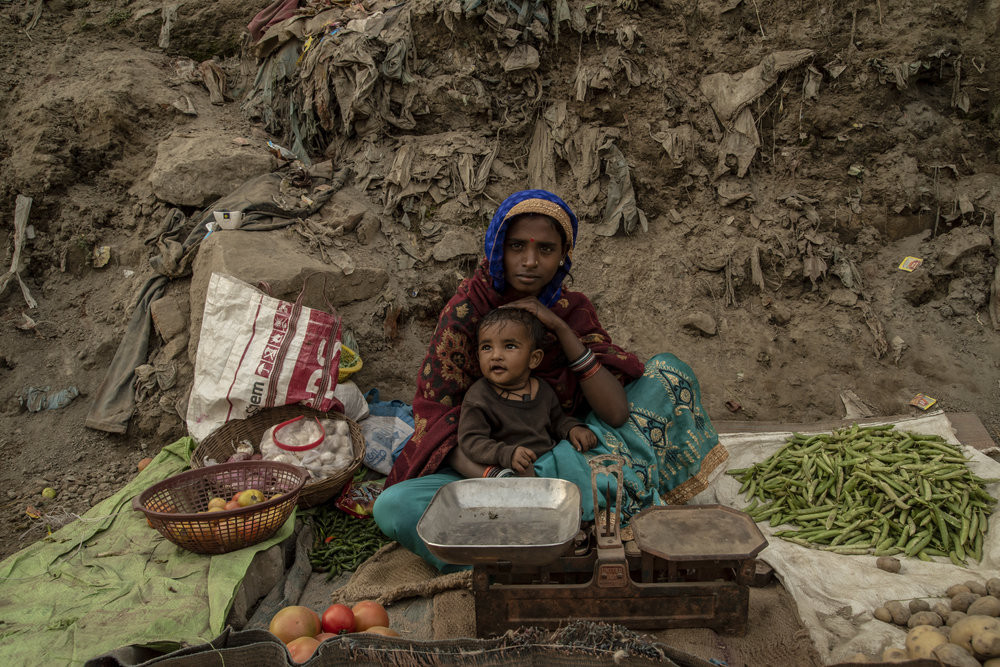 A mother sits with her toddler and sells produce on a roadside. JP/Tyler Blodgett