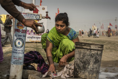 Woman cleans clothes at the roadside faucet. JP/Tyler Blodgett
