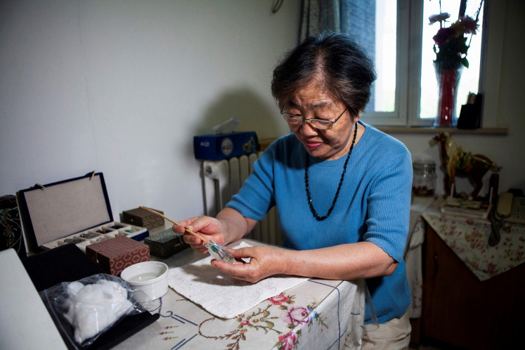 This picture taken on July 1, 2019 shows artist Zhang Yuhua painting a snuff bottle at her home in Beijing. Delicate designs painted on the inside of miniature Chinese snuff bottles by artists like Zhang Yuhua and her husband Gu Qun usually feature calligraphy, floral compositions and traditional rural scenes. But to keep alive the centuries-old art known as