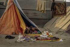 A woman sleeps in a roadside tent as she sells her wares. JP/Tyler Blodgett