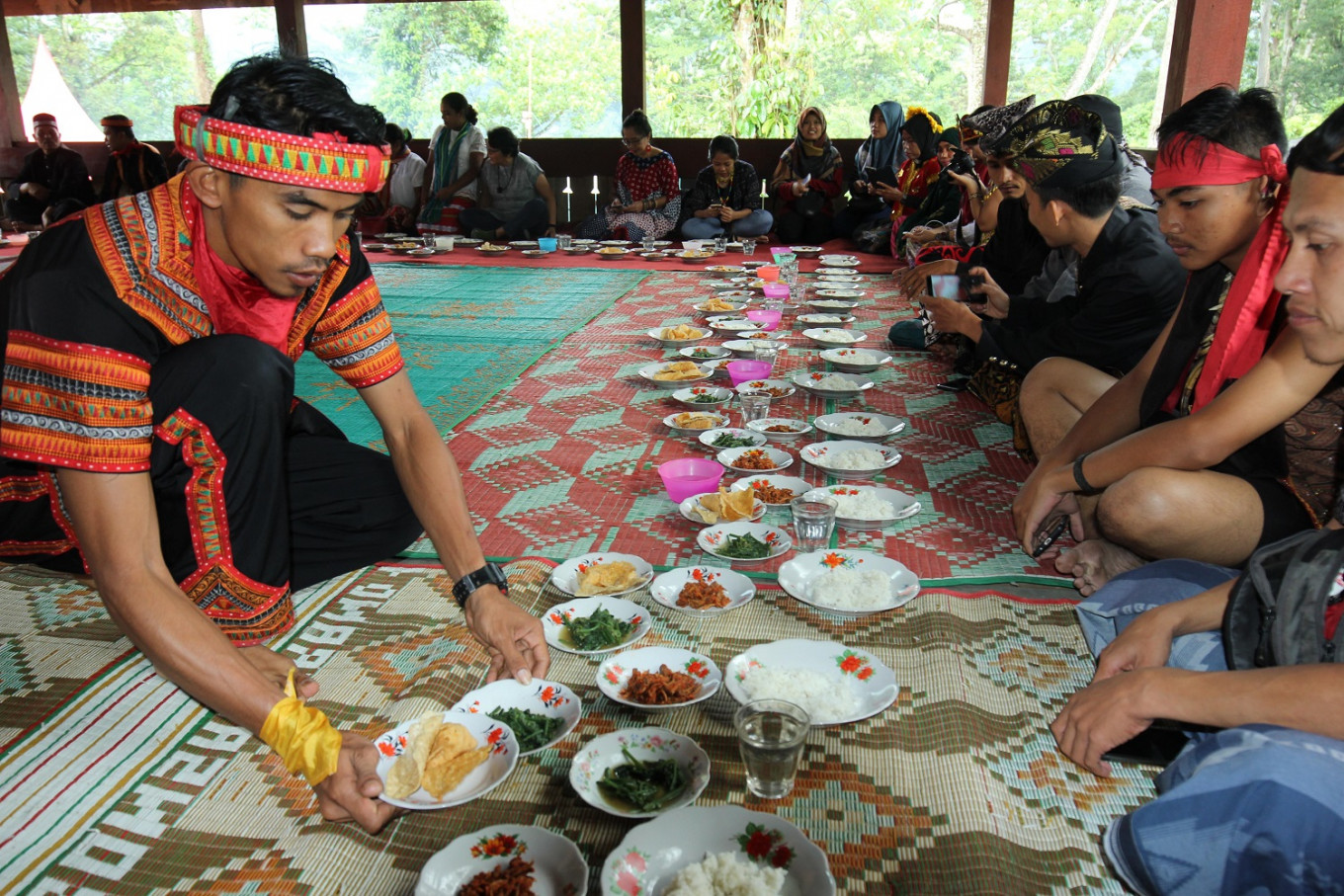A man from Ketambe, Southeast Aceh, serves food to guests at the Archipelago Jamboree in Ketambe village, Aceh, on July 23, 2019.