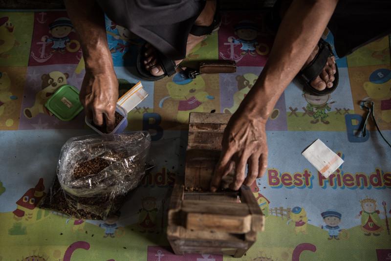 A man rolls a kretek cigarette on a small homemade machine in a warehouse in Parakan. JP/Dottie Bond