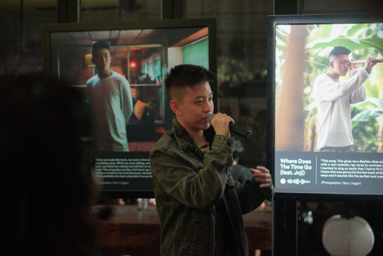 Rich Brian explains about the photos describing his songs during the opening of 'The Sailor Experience' on Aug. 7 at Gudang Gambar in South Jakarta.