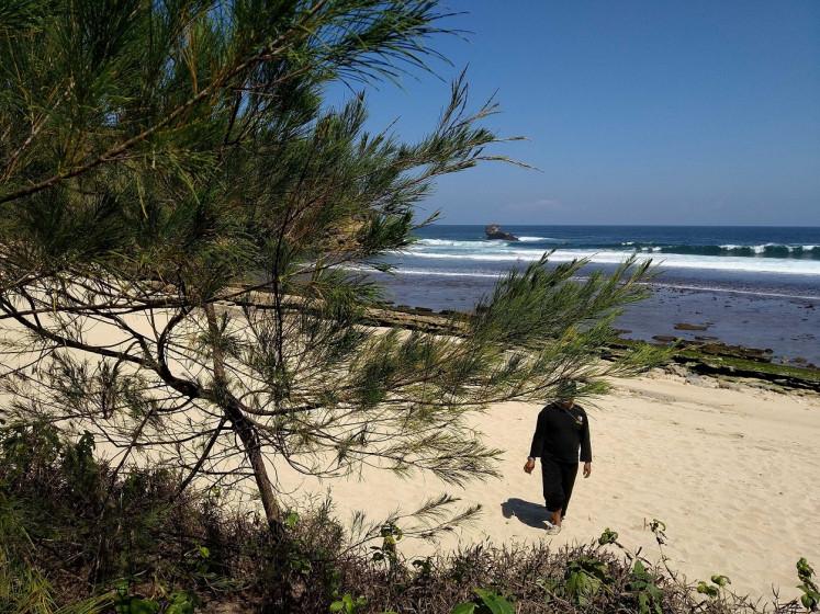A volunteer of Jawa Dipa Nusantara walks on a white sand beach on the southern coast of Blitar, East Java. Jawa Dipa Nusantara is an association focusing on the preservation of the environment and Javanese culture.