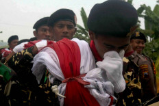 A member of Banser is overcome with emotion while carrying the giant flag. JP/Maksum Nur Fauzan