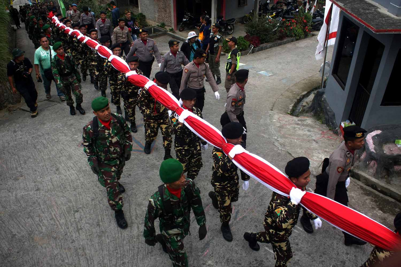 Members of the Indonesian Army (TNI), police and civilian security unit under the Nahdlatul Ulama's Ansor youth wing, Barisan Ansor Serbaguna (Banser), carry a 30-by-40-meter national flag at Sumilir Valley in Karanganyar, Central Java, on Aug. 1. JP/Maksum Nur Fauzan