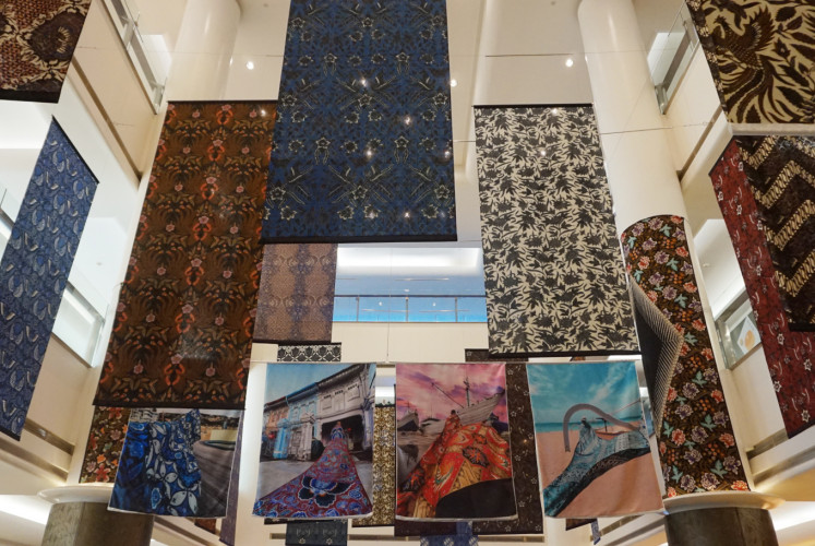 Four photos by JuxDuo, which were printed on duchesse satin fabric, were hung amid batik fabrics by the Iwan Tirta Private Collection.