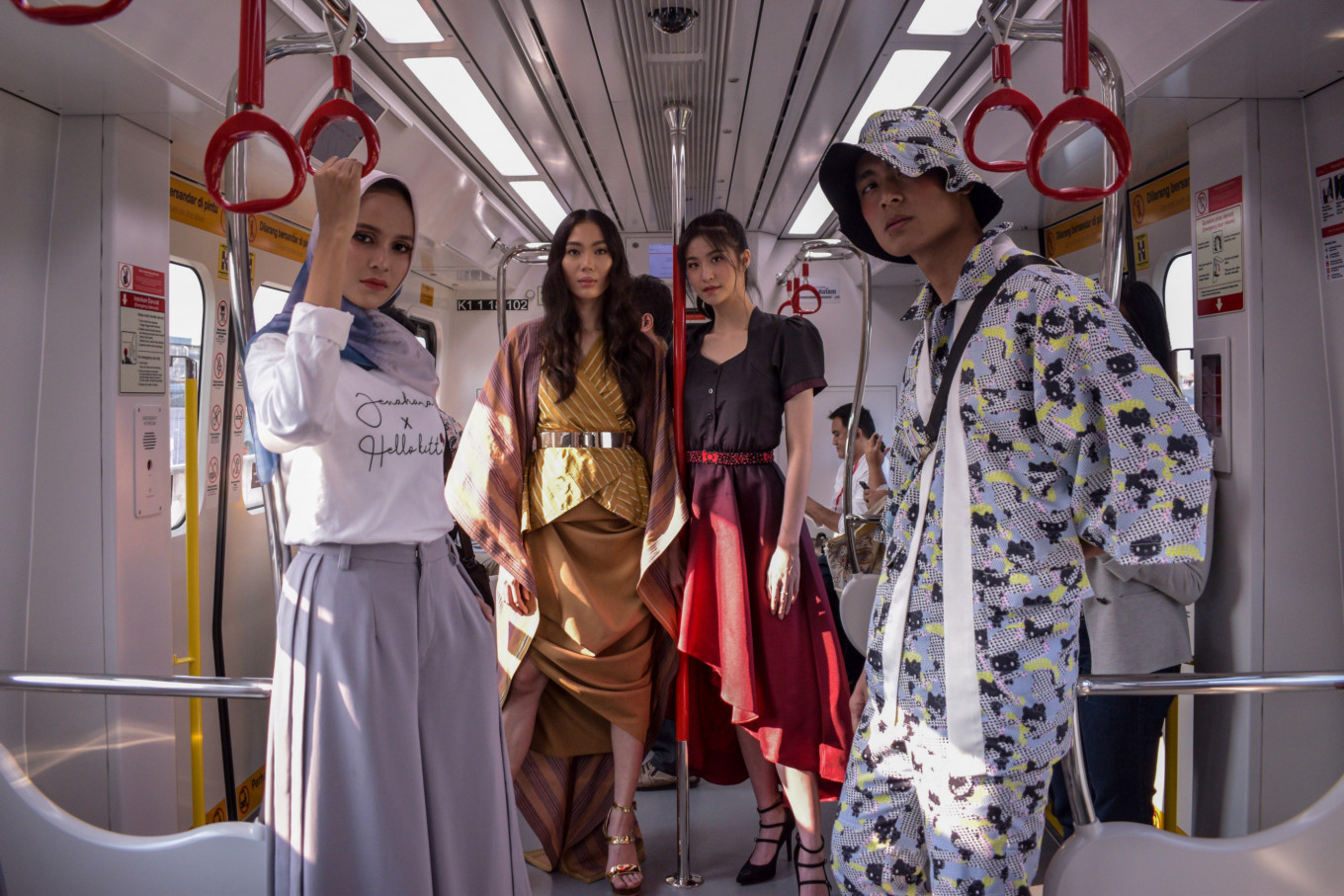 Models wearing outfits from Jenahara (left), Eridani (second left), Cynthia Tan (second right) and AMOTSYAMSURIMUDA (right) during the Fashion Preview inside an LRT Jakarta train. The event was held  as part of the Jakarta Fashion & Food Festival on Aug. 13.