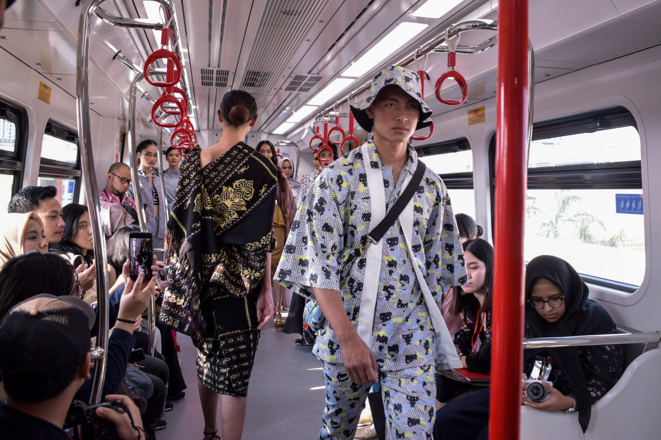 A model wears an outfit from AMOTSYAMSURIMUDA in collaboration with Hello Kitty on an LRT train during the Fashion Preview on Aug. 13.