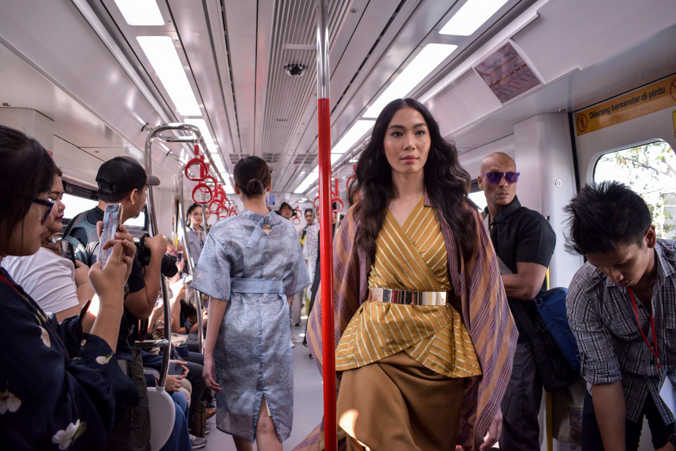 A model walks down the aisle of an LRT Jakarta train, wearing an outfit designed by Eridani.