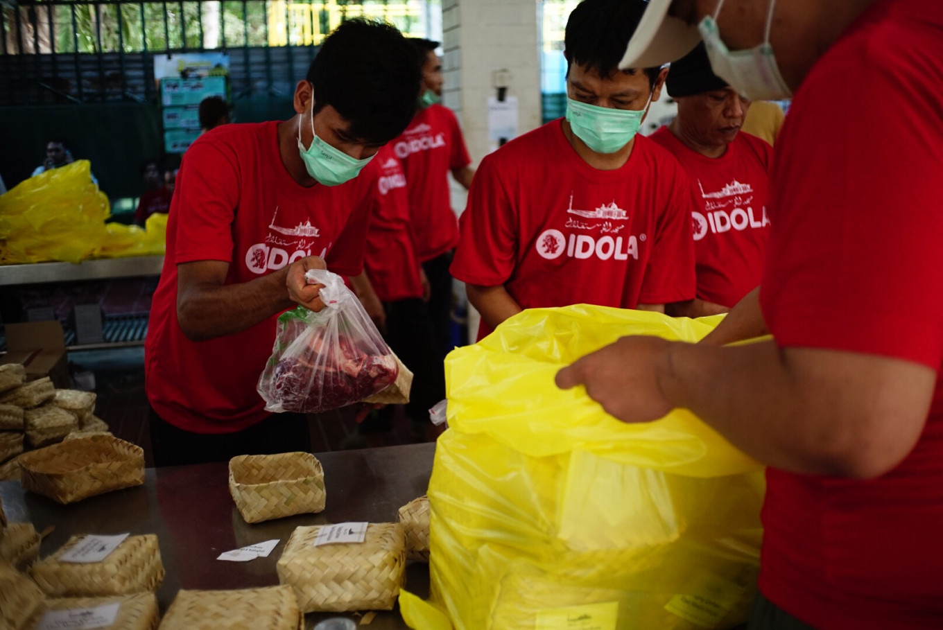 An attendant uses bamboo besek (containers made of plaited bamboo) to hold qurban (sacrificial) meat at Istiqlal Mosque in Central Jakarta on Sunday. The mosque chose not to use plastic bags to distribute its qurban meat for this year's Idul Adha. JP/Syelanita