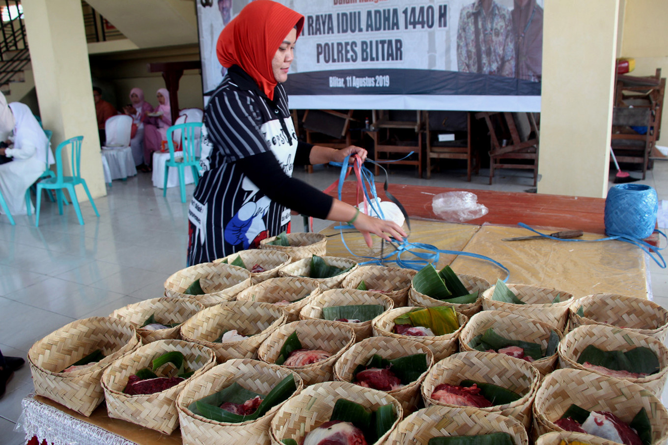 A woman prepares qurban (sacrificial) meat in besek (containers made of plaited bamboo) to be distributed to the public on Sunday at the Blitar Police headquarters in Blitar, Talun district, East Java. The Blitar Police also promoted the use of besek in distributing qurban meat to reduce plastic waste. JP/Asip Hasani