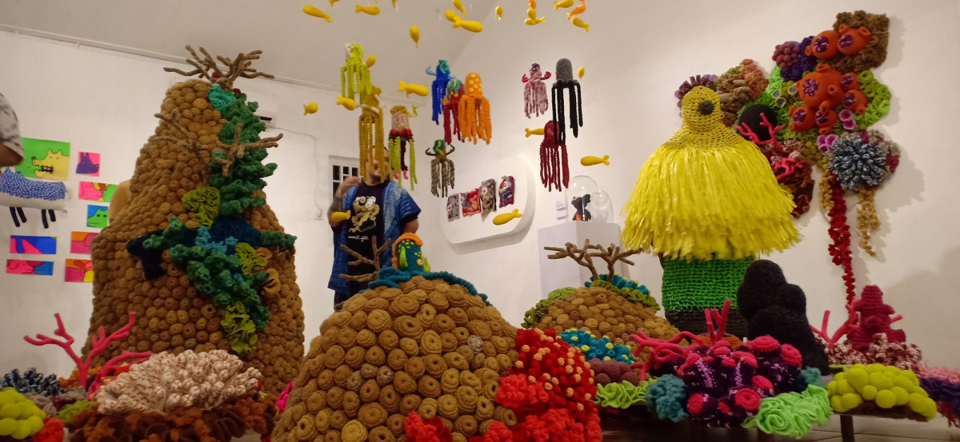 Ayunda Adhisti poses in a yellow monster costume made of knitted plastic rope at Monster Day at Mogus Lab, Yogyakarta.