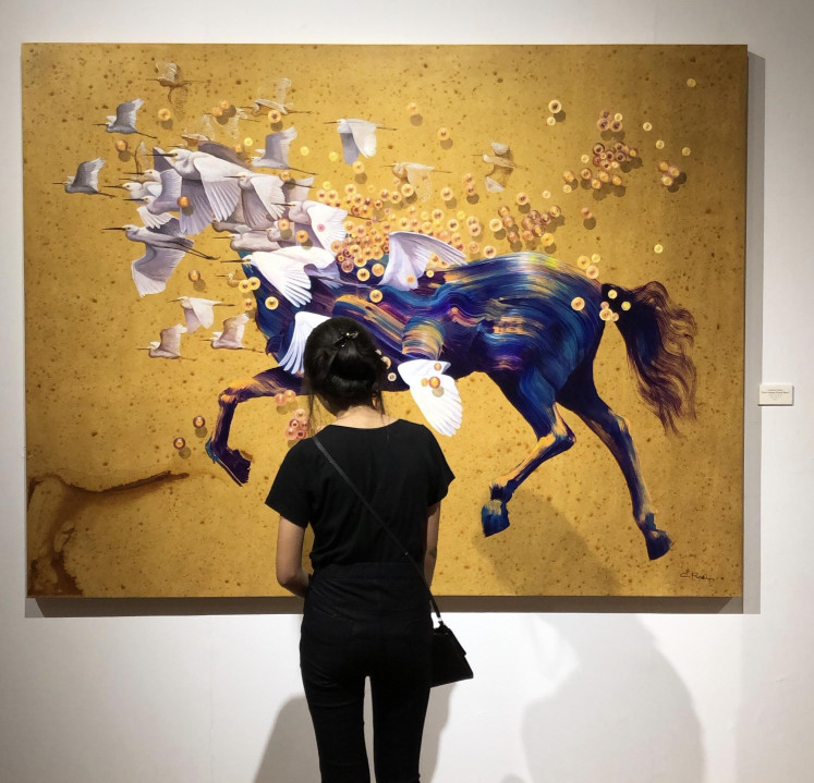 A visitor views the 'Spirit Holopis Kuntul Baris' painting by Choerodin Roadyn at the 'Power of Jawa' exhibition at Bentara Budaya Jakarta.