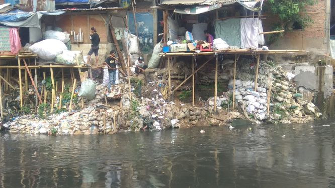 Ciliwung riverbank residents pile up sacks of stones as 'reclamation' for extra space