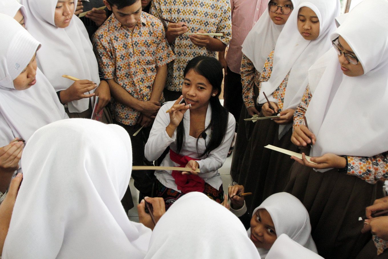 Udayana University student Siti Noviali (center) explains the right way to hold a knife for writing on a palm leaf, called pangrupak, during a workshop at the Ajip Rosidi Library on Thursday. Durable palm leaves were long used in the archipelago to write script. JP/Arya Dipa