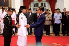 "President Joko ""Jokowi"" Widodo puts a belt on Dewa Agung Ayu Alamanda Diastari at the inauguration of the national flag-hoisting team at the State Palace on Aug. 15. JP/Seto Wardhana"