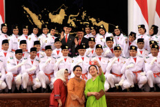 First Lady Iriana (center); Mufidah Kalla, wife of Vice President Jusuf Kalla; and Coordinating Human Development and Culture Minister Puan Maharani pose with members of the national flag-hoisting team during the inauguration of the team at the State Palace on Aug. 15. JP/ Seto Wardhana
