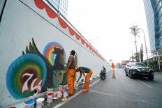 "Jakarta's Public Facility Maintenance Agency workers, often referred to as ""orange troops"", draw the Bhinneka Tunggal Ika (Unity in Diversity) symbol on Slipi Jaya overpass in West Jakarta, on Aug. 17. JP/Donny Fernando"