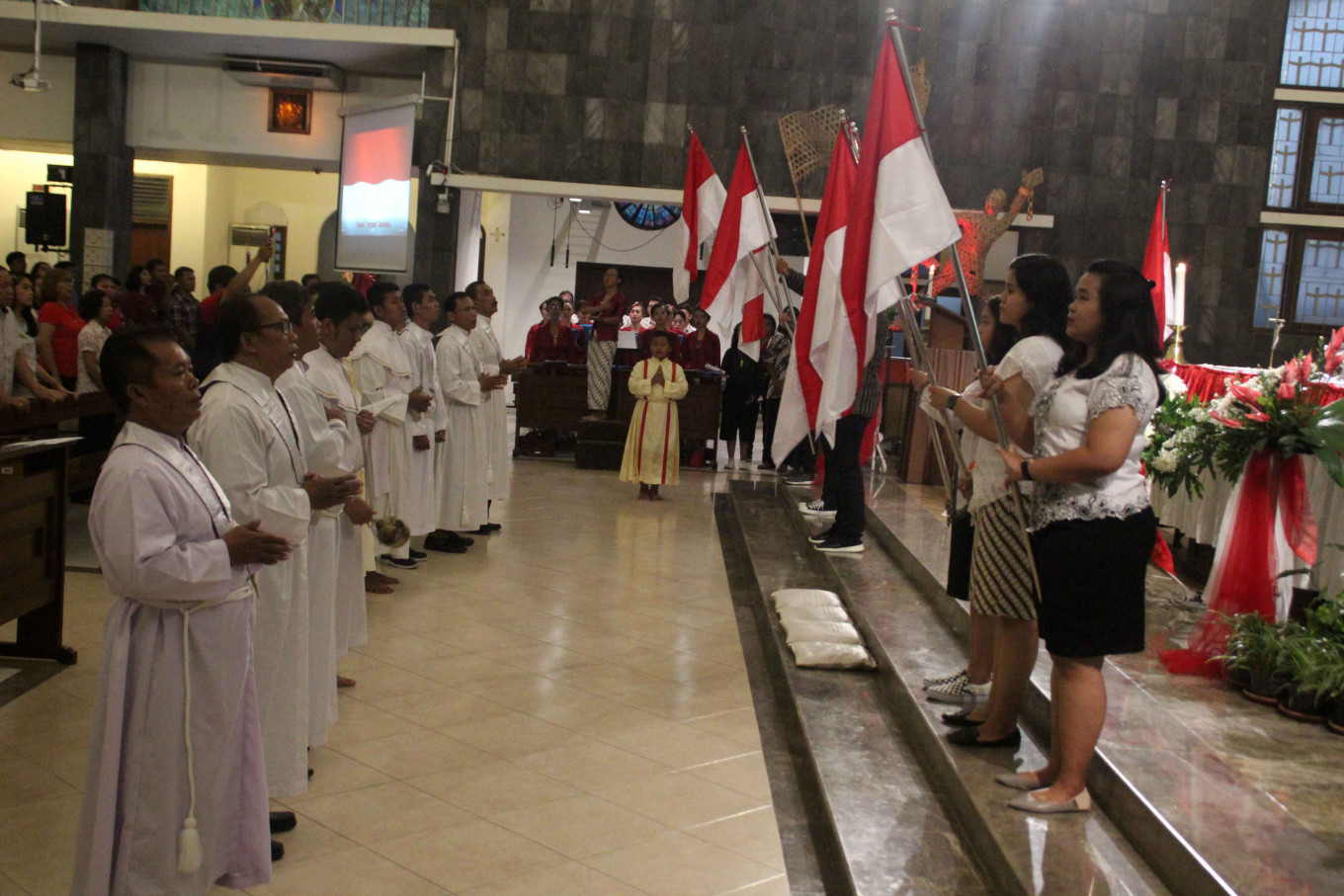 The congregation of St. Theresia Bongsari Catholic Church in Semarang holds a mass to celebrate Indonesia's Independence Day on Aug. 17. Altar boys carry the national flag and the church choir sings the national anthem in its three stanzas. JP/Suherdjoko