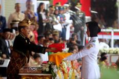 "President Joko ""Jokowi"" Widodo hands over the national flag to national flag-hoisting team member Salma El Mutafaqqiha Putri Achzaabi at the Independence Day ceremony in Jakarta on Aug. 17. JP/Seto Wardhana"