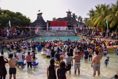 Visitors of Atlantis Water Adventures at Ancol Dreamland Park in North Jakarta observer a giant flag-hoisting ceremony in the pool area on Saturday.JP/Anggie Angela