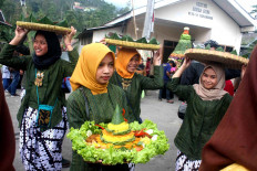 Young women carry tumpeng (cone-shaped steamed rice decorated with different side dishes JP/Maksum Nur Fauzan
