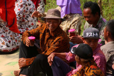 Villagers wait for a parade to pass by while sipping cups of tea. JP/Maksum Nur Fauzan