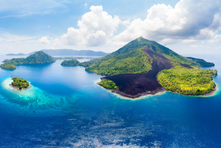 An aerial view of the Banda Islands. The lava flow of the active volcano Banda Api can be seen from afar.