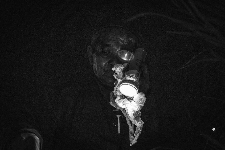 Jumiyo uses a flashlight amid the darkness of Alun-alun Selatan. JP/Anggertimur Lanang Tinarbuko