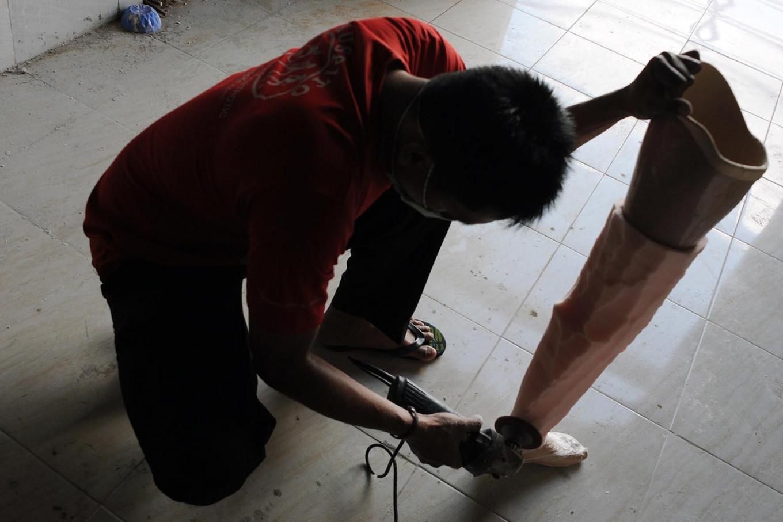 A prosthetic maker smooths an artificial leg. JP/Magnus Hendratmo