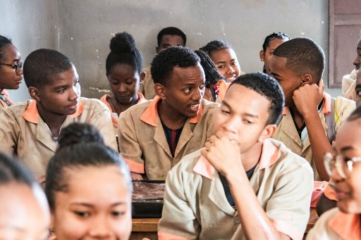 Michael Beafara (rear, center), a Muslim student speaks with a friend during a class at the Saint-Jean Catholic High School, a school that accepts also pupils of Muslim religion, on July 26, 2019 in Antsiranana also known as Diego-Suarez.