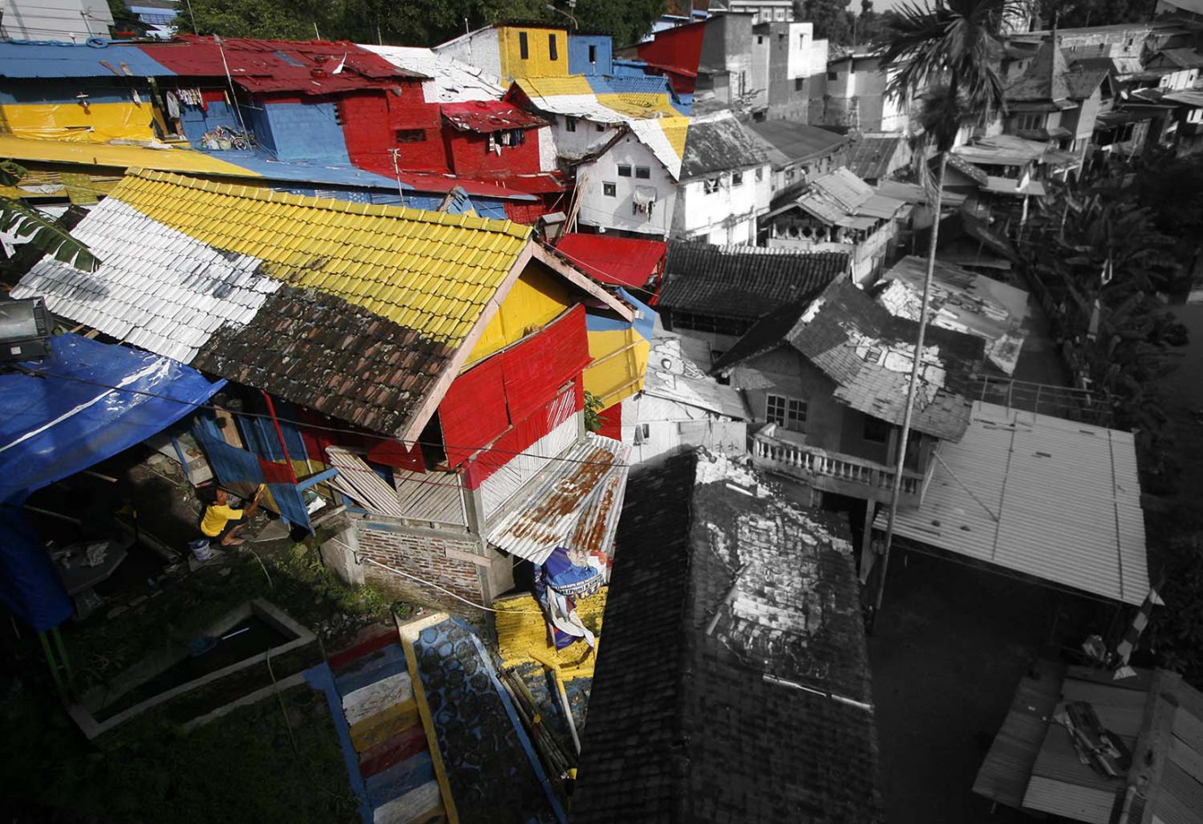 (Left) A resident paints his house in 2015. (Right) In 2019, the colors on the roofs have started to fade. JP/Boy T Harjanto
