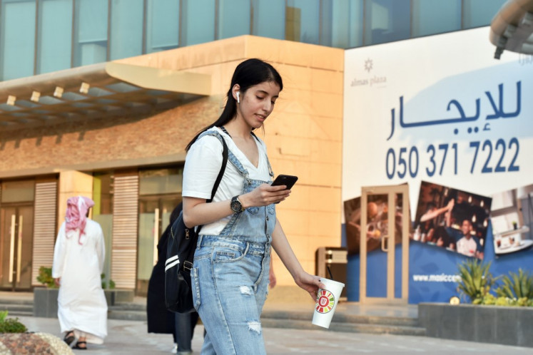 Saudi Manahel al-Otaibi, a 25-year-old activist, checks her mobile as she walks in western clothes in the Saudi capital Riyadh's al Tahliya street on September 2, 2019.