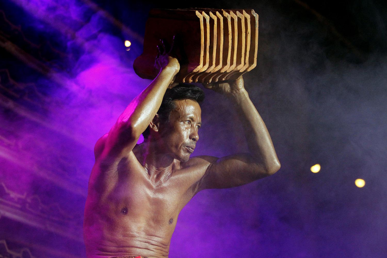 A competitor flaunts his biceps by lifting a number of roof tiles during the 2019 Jatiwangi Cup bodybuilding championship at the Dua Saudara jebor in Burujul Kulon, Majalengka, West Java, recently. The winner of the championship is not allowed to compete in the next championship. JP/Arya Dipa