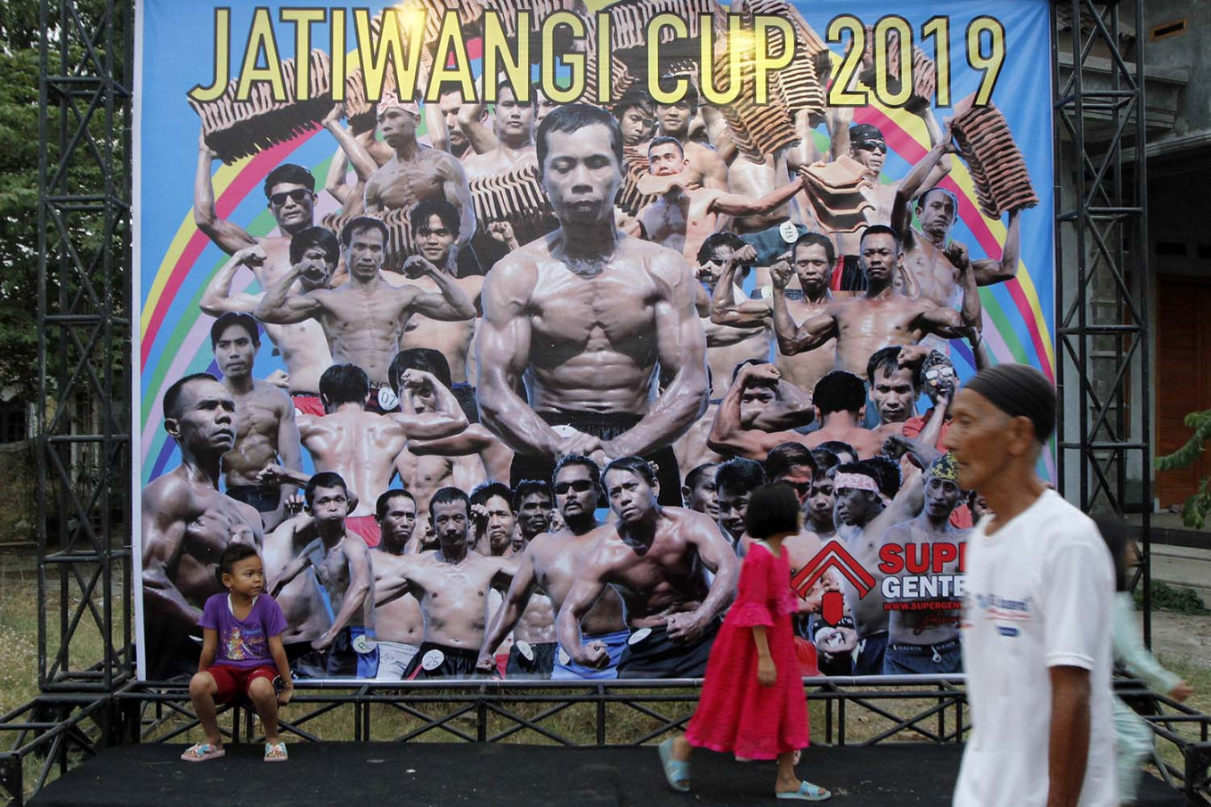 People pass the entrance door of the Dua Saudara jebor in Burujul Kulon, Majalengka, West Java, where the 2019 Jatiwangi Cup bodybuilder championship was being held as a way of improving solidarity among the workers of some 200 traditional roof tile factories in Jatiwangi district. JP/Arya Dipa