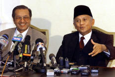 Indonesian President B. J. Habibie (R) gestures as he answers a question while Malaysian Prime Minister Mahathir Mohamad looks on, during a press conference at the latter's office in Putrajaya 25 August 1999. Habibie, who is on a short visit to Malaysia, told reporters that he was anxious to know the outcome of the investigations into the Bank of Bali scandal. AFP/Jimin Lai