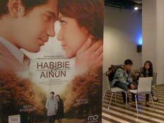 Teenagers wait for a film screening near the poster of Habibie & Ainun at the CGV Cinema - Teraskota in South Tangerang, Banten, on January 19, 2012. JP/ R. Berto Wedhatama