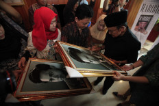 Indonesia's third president BJ Habibie signs a picture of a younger version of himself during the launch of the Habibie Series book at the Habibie and Ainun Library in Jakarta on June 23, 2016. The launch was in conjunction with BJ Habibie's 80th anniversary. JP/Dhoni Setiawan