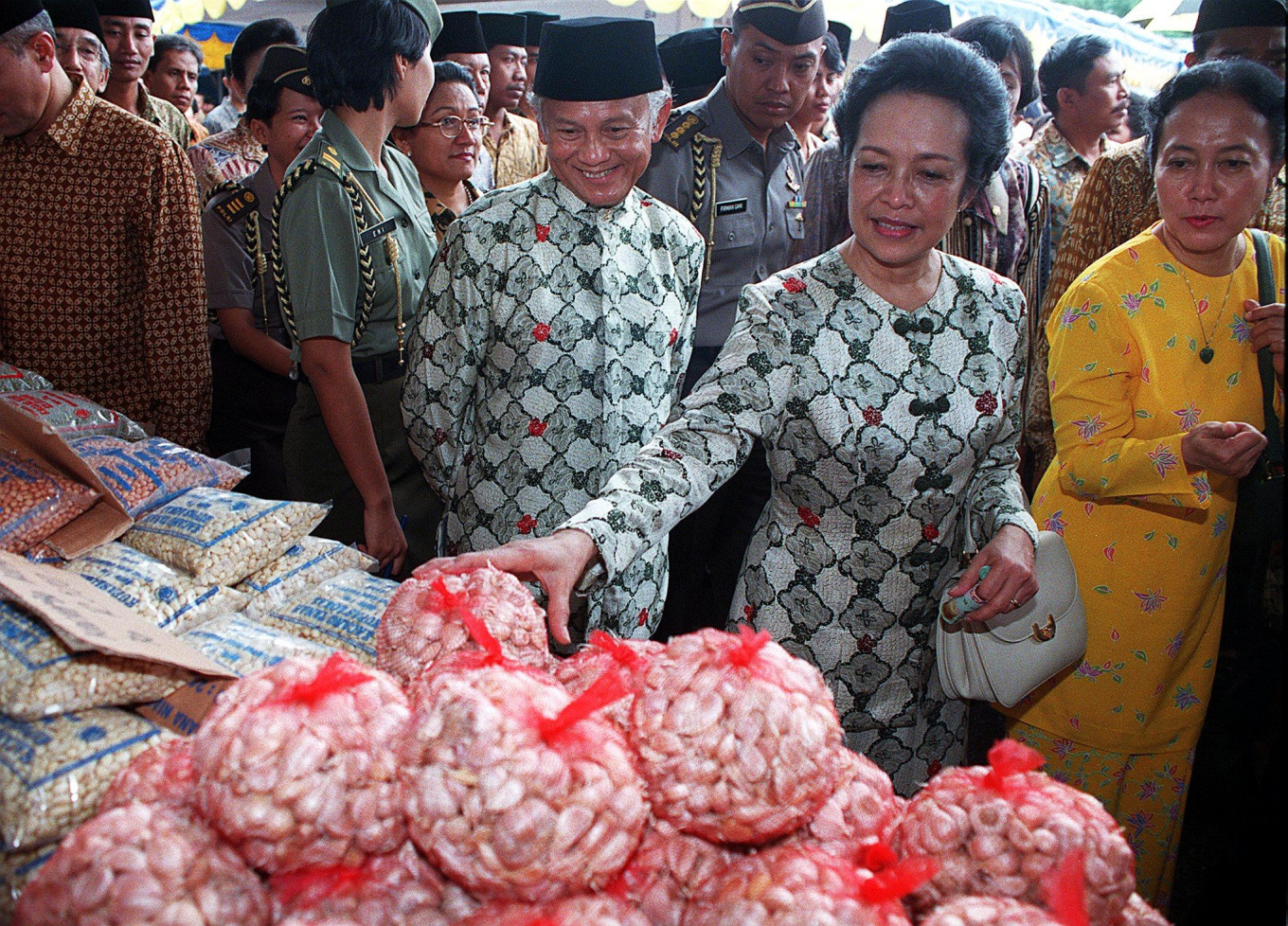 Hasri Ainun Habibie and her husband, Indonesian President B.J.Habibie (C), examine garlic at a cheap market set up in the National Monument Park in Jakarta, 09 January. Food and other basic needs are being offered at discount prices during the three-day event, which was opened by Hasri on Saturday. AFP/Kompas