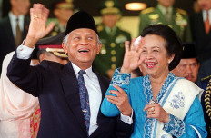 Indonesian President B.J. Habibie and his wife, Hasri Ainun wave to journalists outside the Parliament building in Jakarta 01 October 1999 shortly after attending a swearing in ceremony for new members of Parliament.  The 700 members of the People's Consultative Assembly (MPR) and 500 member's of the People's Representative Council (DPR) were sworn in amid tight security and heavy pressure from opposition parties to shrink six-week timetable and move swiftly to the selection of a successor to President B.J. Habibie. AFP/Str