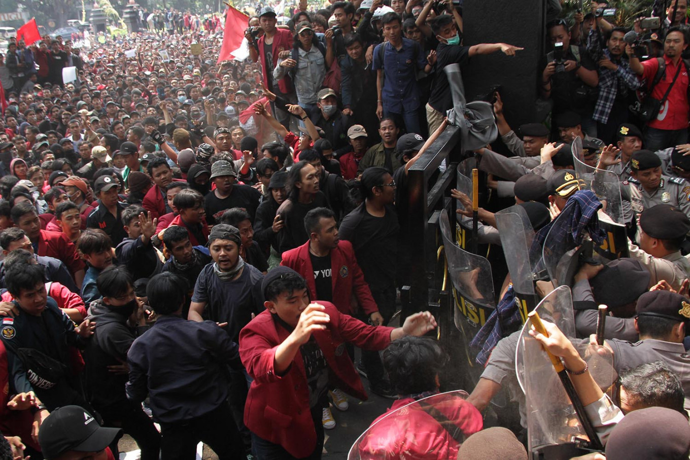 University students in Malang push against a barricade of police officers in an attempt to enter the Malang Legislative Council compound in Malang, East Java, on Sept. 24, during a student protests against the agrarian reform bill and the Criminal Code revision bill. Their attempt led to a clash with the police, with some students and police officers being injured. Antara/Ari Bowo Sucipto
