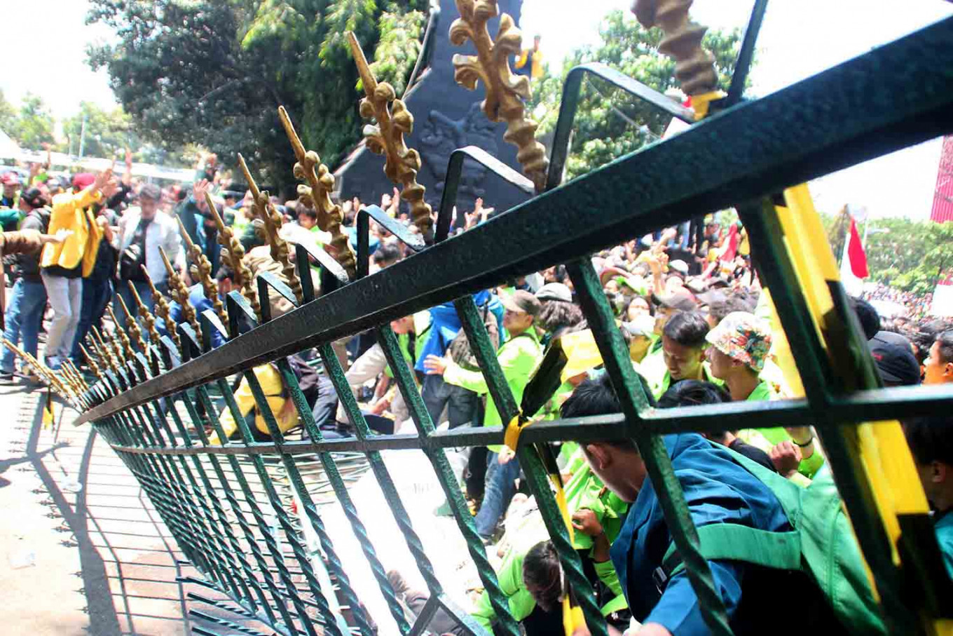 Thousands of university students in Semarang, Central Java, protest against the newly passed Corruption Eradication Commission (KPK) Law and the bill on the Criminal Code. They toppled the gate at the compound where the governor's office and the Central Java Legislative Council are located on Jl. Pahlawan, Semarang, on Sept. 24. JP/Suherdjoko