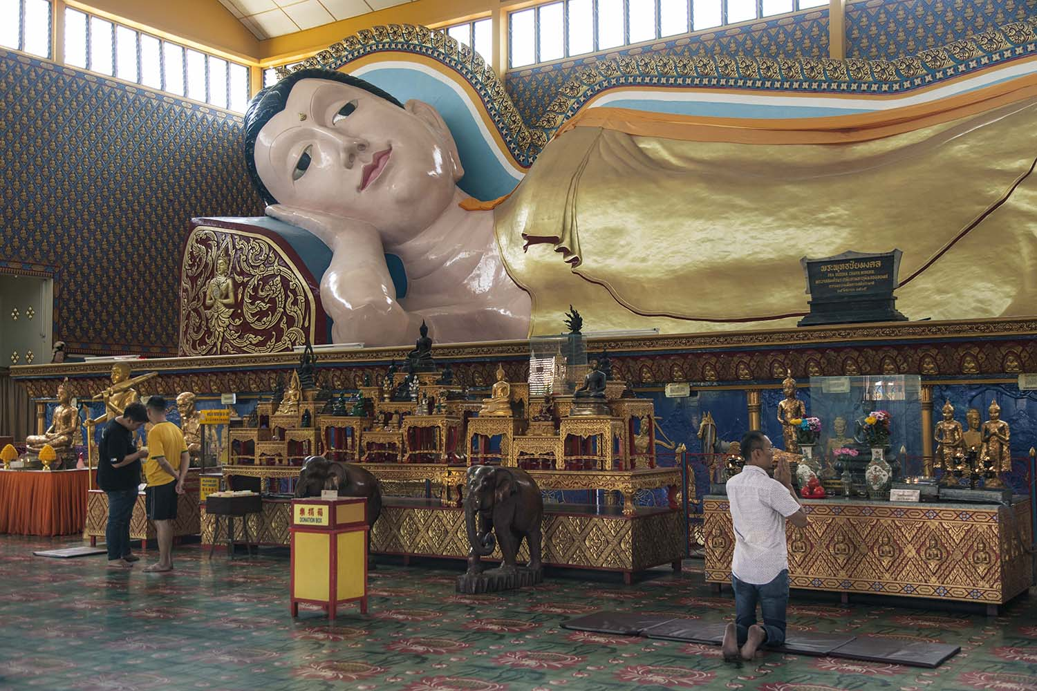 A 33-meter-long reclining Buddha statue is located in the main room of Wat Chayamangkalaram. It is one of the longest reclining Buddha statues in the world. JP/Irene Barlian